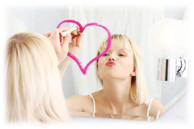 девушка рисует сердечко на зеркале