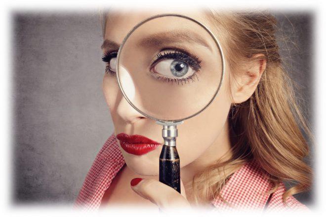 девушка смотрит в увеличительное стекло