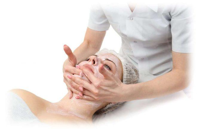 Косметолог наносит на лицо клиентки средство