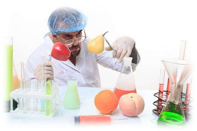 ученый, фрукты и колбы с жидкостью на столе