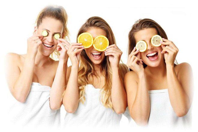 три девушки держат возле глаз кружочки фруктов и огурца