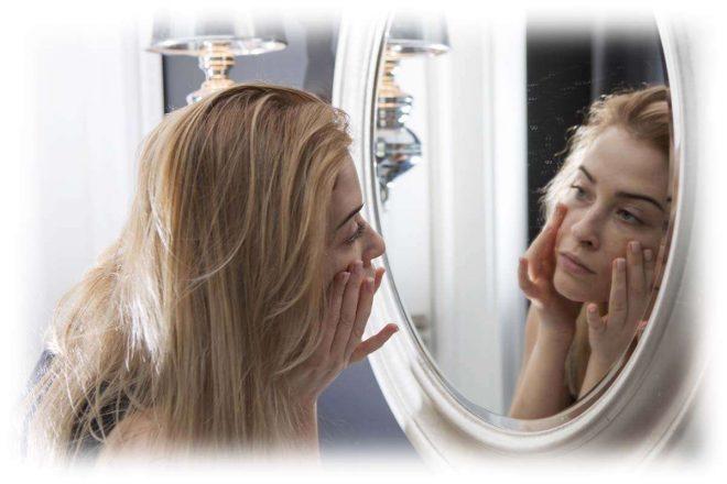 девушка смотрится в зеркало, трогает лицо руками