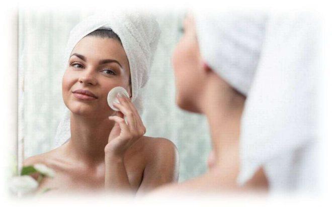 девушка с полотенцем на лице смотрится в зеркало