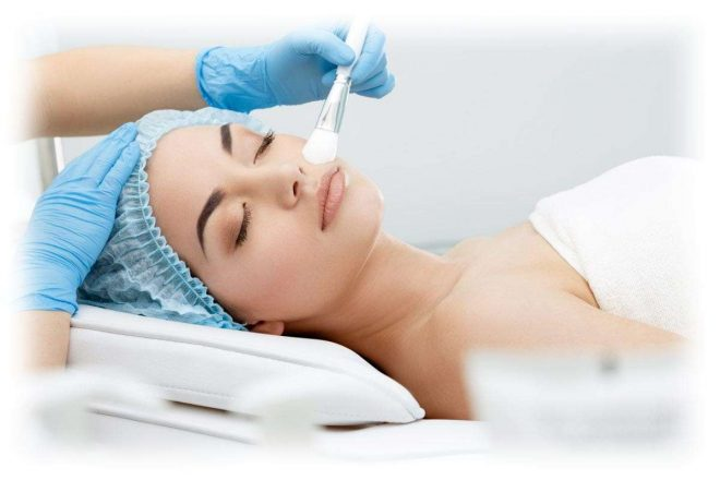 процедура у косметолога, средство наносится кистью на лицо девушки